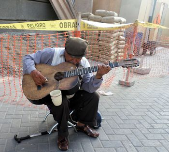 Exploring Lima: Using a homemade mic fashioned from an old telephone handset and wire, mounted inside his guitar, Manuel Pariachi, 72, performs a traditional Huayno song from his Andean homeland, Huancayo