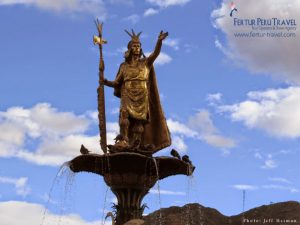 The sun glints off the golden colored statue of Inca Pachacutec in Cusco's main plaza
