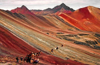 Small tour groups hikes the lower slopes of the multi-colored Vinicunca mountain range