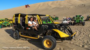 A couple get set to ride in a dune buggy for sandboarding in Huacachina