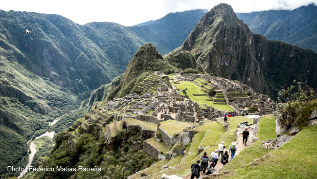 An example of Machu Picchu photography: visitors walking the narrow terrace above the Inca Citadel with the Huayna Picchu peak towering in the background.