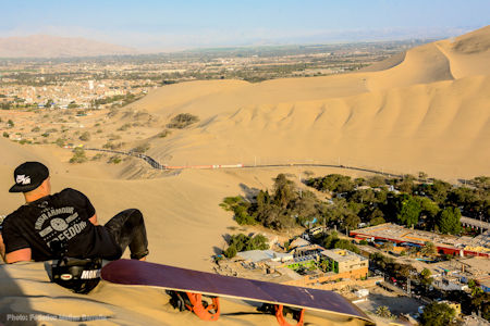 A tourist who has spent the morning sandboarding in Huacachina takes a break to sit on the high dune overlooking the spectacular view of the desert oasis below.