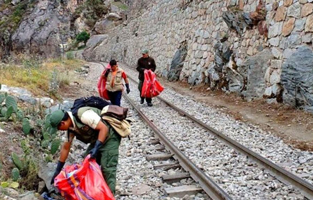 Local residents clean pastic bottles and other waste from the train tracks leading to Machu Picchu.
