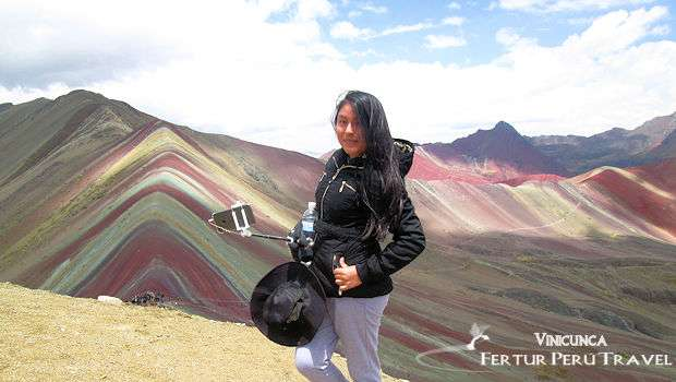 Photo of young woman on top of Rainbow Mountain