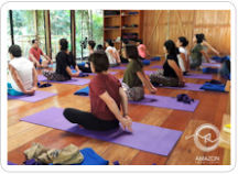 Several people taking part in an afternoon yoga class being taught in the Amazon Yoga Center's large, light-filled studio in on the outskirts of the Tambopata Rainforest Reserve