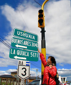 A visitor consults road signs to get her bearings in Ushuaia, the southernmost city in the world, located on the southern shore of Isla Grande de Tierra del Fuego
